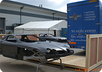 large wooden packing case and maclaren sports car
