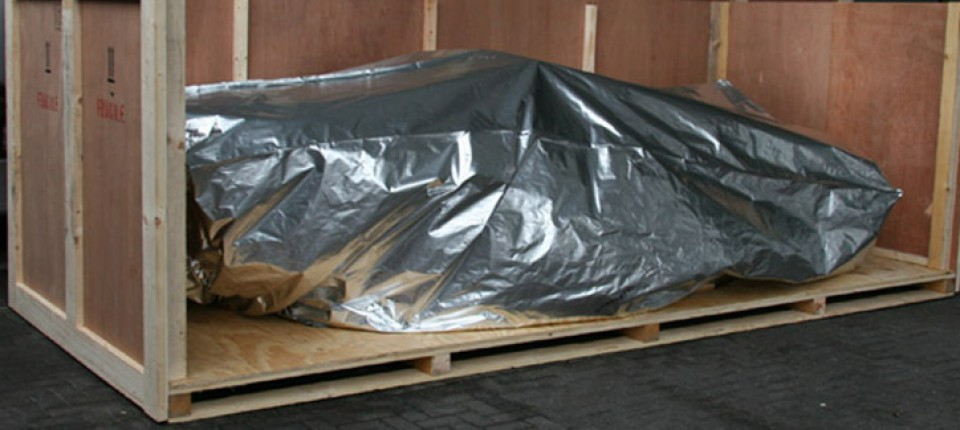 Sports car in wooden packing case with foil wrap for protection