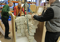 Men packing items in a wooden crate