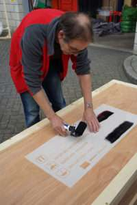 Applying paint to stencil a wooden packing case