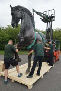 Bronze horse lowered onto base of packing crate
